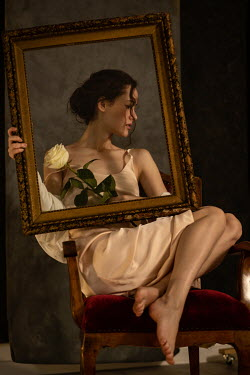 Elena Alferova WOMAN SITTING HOLDING ROSE AND PICTURE FRAME Women