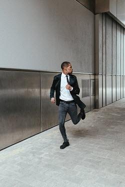 Matilda Delves MAN RUNNING OUTSIDE MODERN BUILDING Men