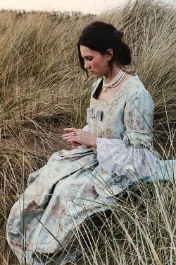 Matilda Delves HISTORICAL BRUNETTE WOMAN SITTING IN SAND DUNES Women