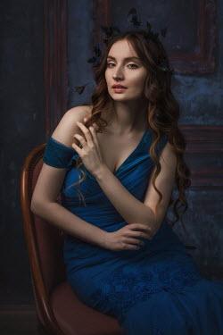 Beata Banach BRUNETTE WOMAN IN BLUE DRESS SITTING INDOORS Women