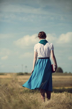 Magdalena Russocka retro woman holding book walking in countryside