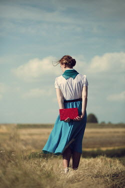 Magdalena Russocka retro woman holding book standing in countryside