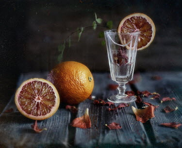 Andreeva Svoboda ORANGES WITH GLASS ON TABLE WITH PETALS Miscellaneous Objects