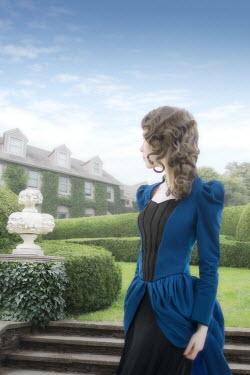 ILINA SIMEONOVA WOMAN WITH BLUE DRESS IN GARDEN WATCHING HOUSE Women