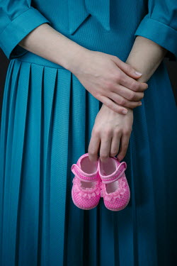 Magdalena Russocka woman holding baby shoes