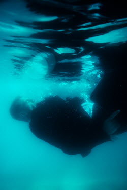Magdalena Russocka man in suit holding briefcase floating under water