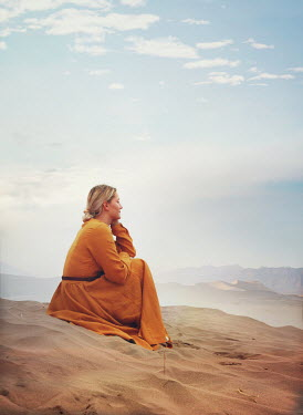 Mark Owen BLONDE WOMAN SITTING IN DUNES WATCHING DESERT Women