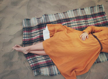 Mark Owen WOMAN IN DRESS LYING ON BLANKET ON SAND Women