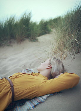Mark Owen BLONDE WOMAN LYING ON RUG IN SAND DUNES Women