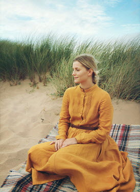 Mark Owen BLONDE WOMAN SITTING ON BLANKET IN SAND DUNE Women