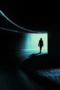Magdalena Russocka modern woman walking down underpass at night