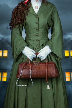 Magdalena Russocka historical woman holding medic bag and stethoscope standing by house with lights in windows at night