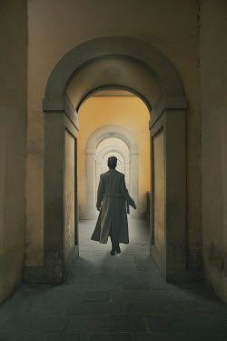 Nic Skerten WOMAN IN COAT WALKING THROUGH ARCHES Women
