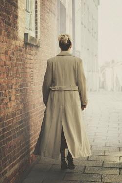Nic Skerten WOMAN WALKING BY BUILDINGS IN FOGGY TOWN Women