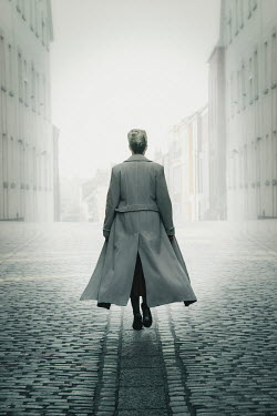 Nic Skerten WOMAN IN COAT WALKING IN FOGGY CITY Women
