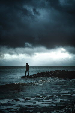 Nic Skerten SILHOUETTED BOY ON ROCKS BY STORMY SEA Men