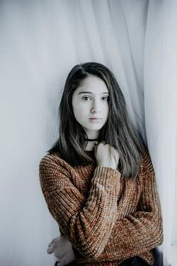 Nic Skerten SERIOUS TEENAGE GIRL WITH BROWN SWEATER INDOORS Children