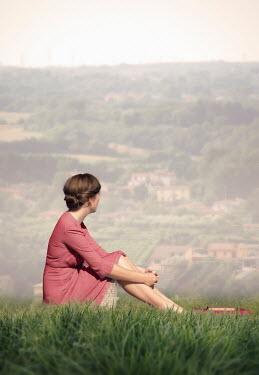Elisabeth Ansley WOMAN SITTING IN FIELD WATCHING VILLAGE ON HILL Women