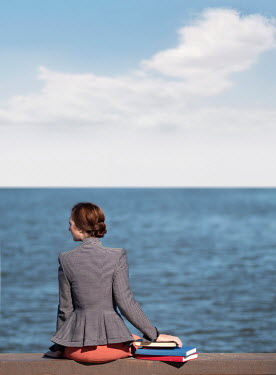 Elisabeth Ansley RETRO WOMAN WITH BOOKS SITTING ON SEA WALL Women