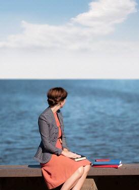 Elisabeth Ansley WOMAN WITH BOOKS SITTING ON SEA WALL Women