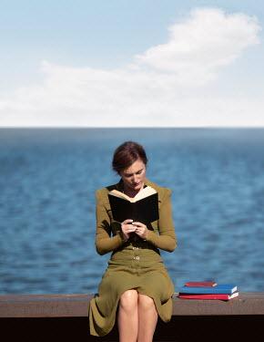 Elisabeth Ansley WOMAN SITTING ON SEA WALL READING BOOK Women