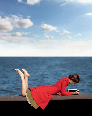 Elisabeth Ansley WOMAN LYING ON SEA WALL READING BOOK Women