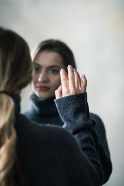 Ildiko Neer Woman looking at herself in the mirror