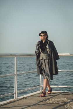 Joanna Czogala RETRO WOMAN IN COAT WALKING BY SEA Women
