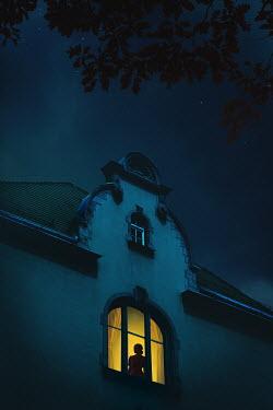 Joanna Czogala SILHOUETTED WOMAN IN WINDOW AT NIGHT Women