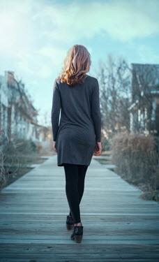 Buffy Cooper Young woman in gray dress walking on boardwalk