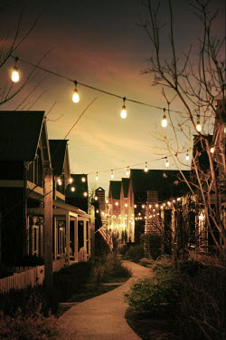 Buffy Cooper Lights hanging over houses during sunset