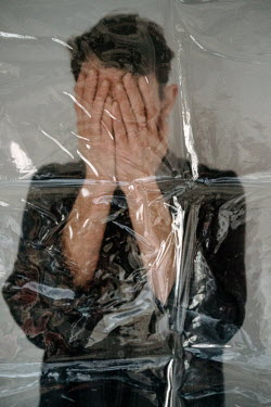 Esme Mai Young man covering his face behind plastic sheet
