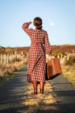 Marie Carr Young woman in 1940s dress with suitcase standing on rural road