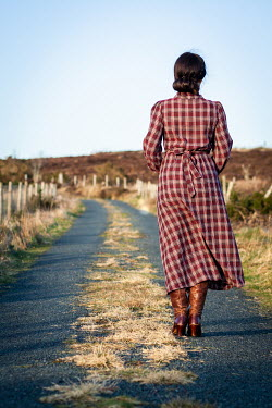 Marie Carr Woman in 1940s checked dress standing on rural road