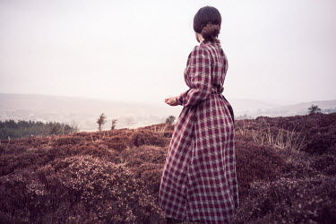 Marie Carr Young woman in 1940s checked dress standing in field