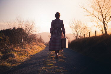 Marie Carr Young woman in 1940s dress with suitcase walking on rural road