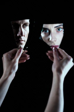Magdalena Russocka faces of woman and man reflected in pieces of broken mirror held by woman's hands