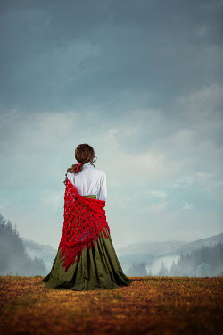 Magdalena Russocka historical woman with red shawl standing in countryside with mountainscape