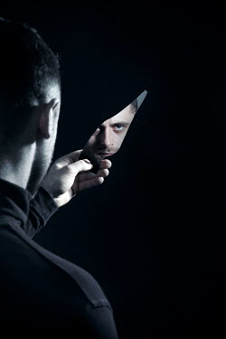 Miguel Sobreira Man holding shard of mirror