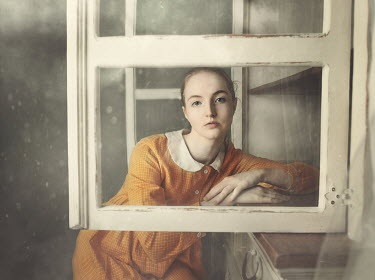 Anna Buczek Young woman in checked yellow dress behind window