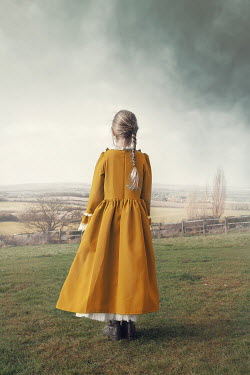 Anna Buczek Victorian girl in yellow dress standing in field