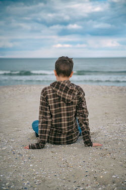 Galya Ivanova Boy in checked hoodie sitting on beach