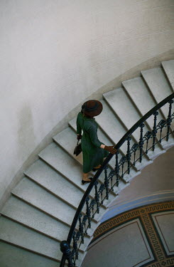 Nikaa Young woman in 1940s hat and coat walking on staircase
