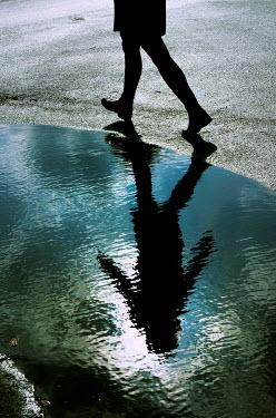 Ute Klaphake REFLECTION OF GIRL WALKING BY PUDDLE Women