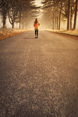 Emma Goulder WOMAN WALKING ON COUNTRY ROAD IN SUNLIGHT Women