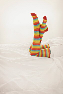 Emma Goulder FEMALE LEGS IN STRIPY TIGHTS LYING ON BED Women