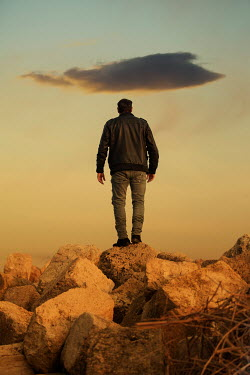 Mohamad Itani MAN ON ROCKS WITH SKY AND CLOUD AT SUNSET Men