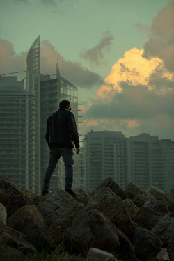 Mohamad Itani MAN ON ROCKS WITH HIGH RISE BUILDINGS AT DUSK Men