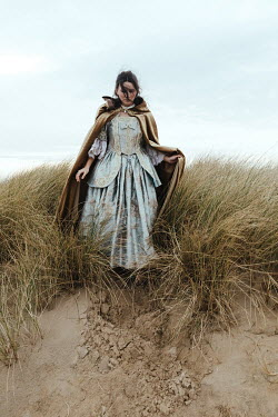 Matilda Delves HISTORICAL WOMAN WITH CAPE STANDING ON SAND DUNES Women