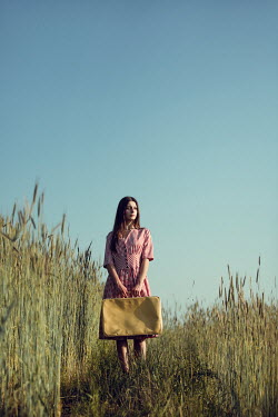 Magdalena Russocka young woman carrying suitcase standing in field of rye